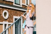 Fotografie stylish happy woman with paper bags talking by phone on stairs