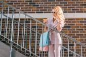 Fotografie stylish young woman talking by phone and holding credit card