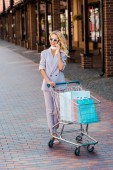Fotografie smiling young woman with shopping cart full of paper bags talking by phone on street