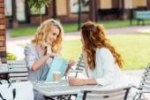 Módní mladé ženy kontrola kupuje při posezení v kavárně po nakupování