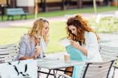 Stylový mladé ženy kontrola kupuje při posezení v kavárně po nakupování