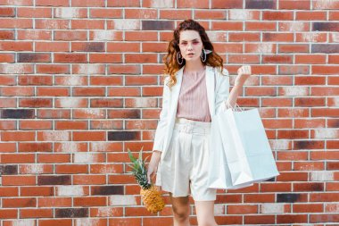 beautiful young woman with pineapple and shopping bags looking at camera in front of brick wall
