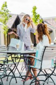 Módní mladé ženy trávit čas spolu v kavárně po nakupování