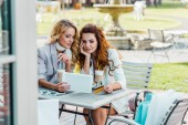 Fotografie fashionable young women with credit card and tablet making e-shopping sitting in cafe