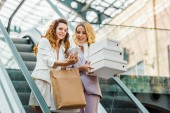 Photo beautiful young women with shopping bags and boxes looking at smartphone on escalator at mall