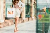 Fotografie Oříznout záběr stylové ženy držící nákupní tašku s prodej znamení na mall