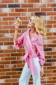 Stylový usmívající se žena v růžové jíst zmrzlinu před cihlová zeď