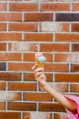 oříznuté shot žena hospodářství lahodné zmrzliny v oplatkovém kornoutku před cihlová zeď