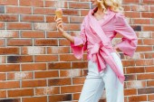 Photo cropped shot of young woman in pink holding ice cream in front of brick wall