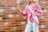 oříznuté záběr mladá žena v růžové hospodářství zmrzlinu před cihlová zeď