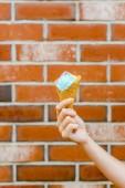 oříznutý snímek žena hospodářství zmrzliny v oplatkovém kornoutku před cihlovou zeď