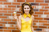 šťastná mladá žena ve žlutém oblečení se zmrzlinou, při pohledu na fotoaparát před cihlovou zeď