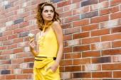 Fotografie módní dívka v žlutých šatech se zmrzlinou pózuje před cihlovou zeď