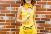 oříznutý snímek usměvavá mladá žena ve žlutém oblečení drží zmrzlinu před cihlovou zeď