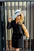 Fotografie atraktivní mladá žena ve stylové sako a klobouk stojící před plot s čerstvou bagetou