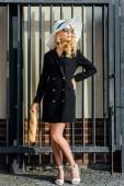 krásná mladá žena v stylové sako a klobouk stojící před plotem s bagetou