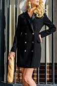 Oříznout záběr atraktivní ženy v elegantní sako, stojící u plotu s bagetou