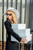 Photo fashionable young woman in stylish clothes holding stack of white shoe boxes