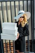krásná mladá žena ve stylovém oblečení drží stoh krabic na bílé boty