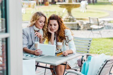 fashionable young women with credit card and tablet making e-shopping sitting in cafe