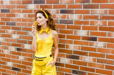 stylish young woman in yellow clothes eating ice cream in front of brick wall