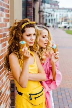 beautiful young women in colorful clothes eating delicious ice cream on street