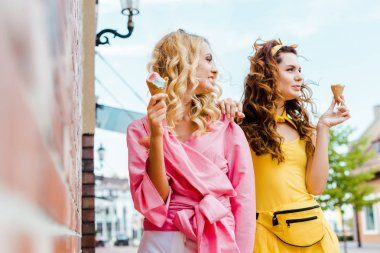 beautiful young women in stylish  colorful clothes eating ice cream on street