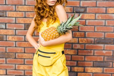 Cropped shot of young woman in yellow clothes holding pineapple in front of brick wall stock vector