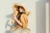 stylische junge Frau mit Strohhut steht vor weißer Wand und isst französisches Baguette