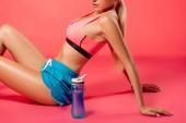 cropped image of sportswoman posing on floor near sport bottle on red