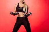 zugeschnittenes Bild der Sportlerin training mit Hanteln isoliert auf rot