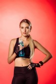 Fotografie attractive sportswoman holding sport bottle with water and looking at camera isolated on red