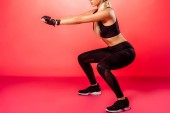 cropped image of sportswoman training and doing squats on red