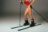 částečný pohled ženy v červených plavkách, šátek s lyžařskou výbavu na šedém pozadí