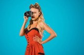 beautiful woman in retro dress with photo camera isolated on blue