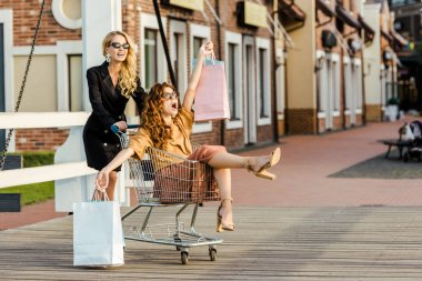 beautiful young women riding shopping cart during shopping together