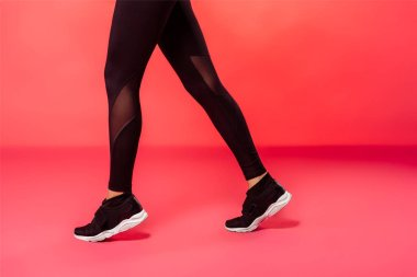 cropped image of sportswoman walking in black leggings on red