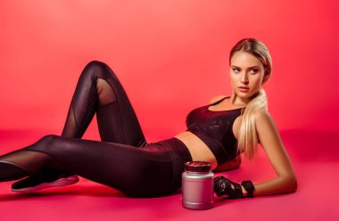 attractive sportswoman lying with sport supplement jar on red