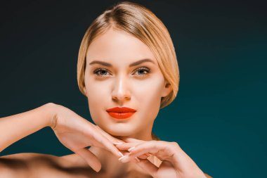 portrait of beautiful young woman with red lips looking at camera on dark background