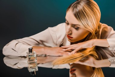 portrait of stylish blond woman looking at perfume on mirror surface with reflection on dark background