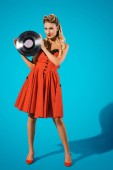 mladí pin se žena ve stylové vintage šaty s vinylových desek na modrém pozadí