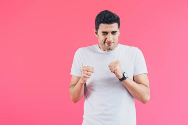 scared handsome man with closed eyes standing with fists isolated on pink