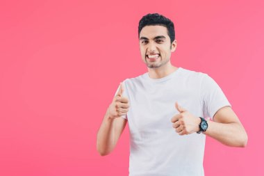grimacing smiling man showing thumbs up isolated on pink