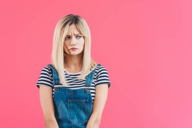 worried beautiful girl in denim overall looking away isolated on pink