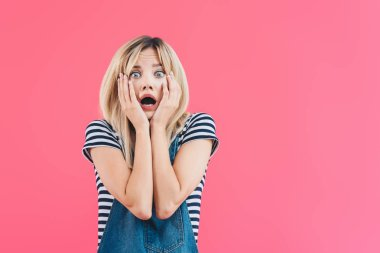 shocked girl in denim overall touching face and looking at camera isolated on pink