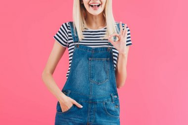 cropped image of smiling girl in denim overall showing okay gesture isolated on pink