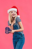 Fotografie portrait of smiling woman in santa claus hat with heart shaped gift isolated on pink