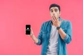 Šokovaný mladý muž pokrývající ústa rukou a ukazuje iphone smartphone izolované na růžové