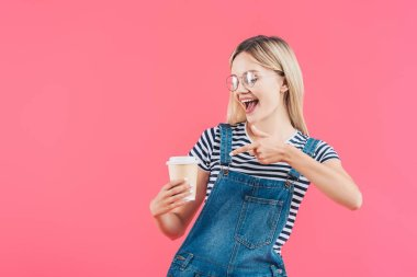 Portrait of young woman pointing at coffee to go in hand isolated on pink stock vector