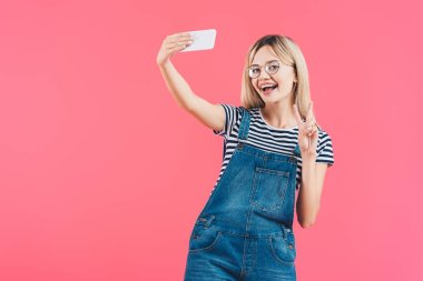 Portrait of woman showing peace sign while taking selfie on smartphone isolated on pink stock vector
